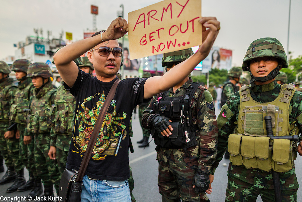 26 MAY 2014 - BANGKOK, THAILAND:  A man stands in front of soldiers protesting against the coup in Thailand at Victory Monument during a pro-democracy rally in Bangkok. About two thousand people protested against the coup in Bangkok. It was the third straight day of large pro-democracy rallies in the Thai capital as the army continued to tighten its grip on Thai life.    PHOTO BY JACK KURTZ
