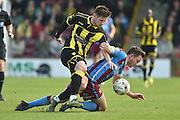 Tom Hopper of Scunthorpe United brought down by Burton Albion defender Calum Butcher (12)  during the Sky Bet League 1 match between Scunthorpe United and Burton Albion at Glanford Park, Scunthorpe, England on 9 April 2016. Photo by Ian Lyall.