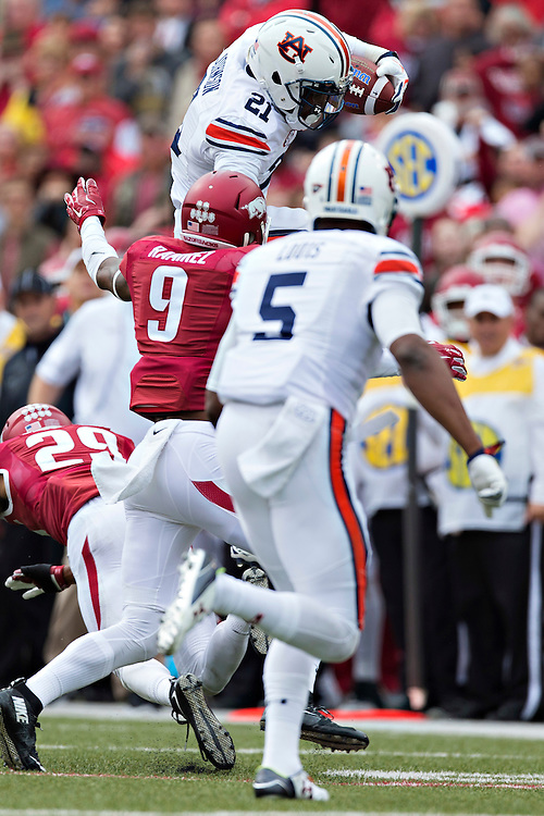 FAYETTEVILLE, AR - OCTOBER 24:  Kerryon Johnson #21 of the Auburn Tigers jumps over a defender to avoid the tackle during a game against the Arkansas Razorbacks at Razorback Stadium Stadium on October 24, 2015 in Fayetteville, Arkansas.  The Razorbacks defeated the Tigers in 4 OT's 54-46.  (Photo by Wesley Hitt/Getty Images) *** Local Caption *** Kerryon Johnson