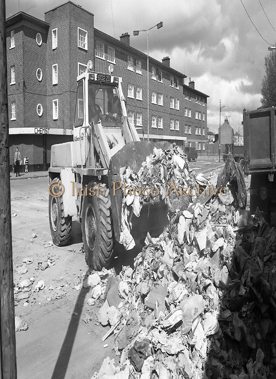 Army Removes Refuse In Dublin..1986..05.06.1986..06.05.1986..5th June 1986..Due to the ongoing strike by Dublin Corporation workers,the army were called in to help clear some of the mounds of rubbish stacking up around the city. Health worries from the rotting rubbish and the danger of rat infestation caused the intervention. The 2nd Garrison Supply and Transport Company,McKee Barracks,Dublin were delegated to clear the rubbish from St Theresa's Flats,Donore Avenue,Dublin...Picture shows soldiers operating the bulldozer to clear some of the rubbish building up around the city.