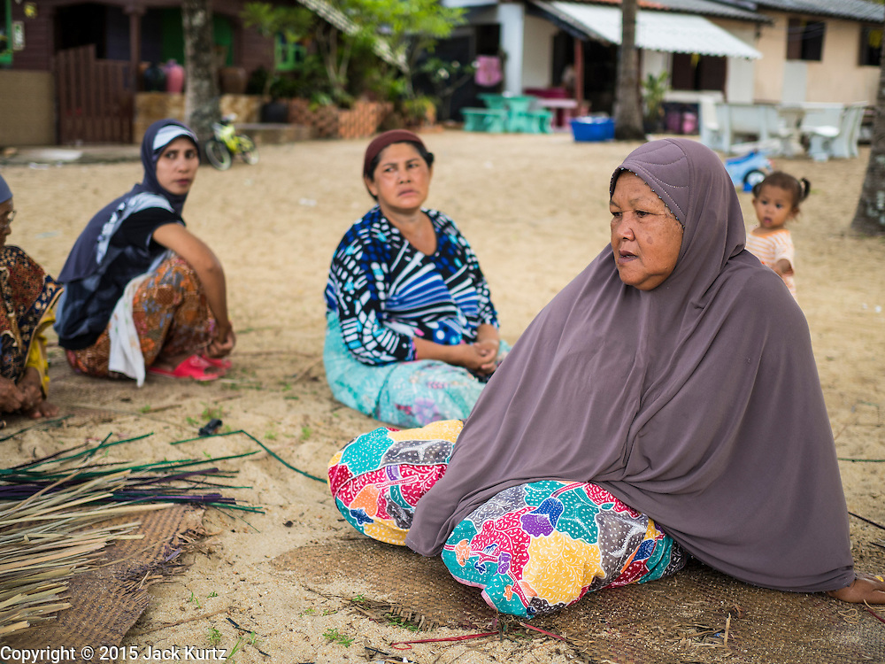 15 JUNE 2105 - BAN THONG, NARATHIWAT, THAILAND: Wives of fisherman socialize under palm trees on Ban Thong beach in Narathiwat.       PHOTO BY JACK KURTZ