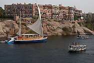 The hotel old and new cataract. The nile river and the cataracts, boats, fellucas, islands in Aswan. cruise on a Sandal  boat, traditional boat transformed in a cruise boat) on the nile river in  Asswan  Egypt   / l'hotel old and new cataract.; le nil, les bateaux, les cataractes, les iles a Assouan. croisiere sur un Sandal, Bateau de croisiere  tradionnel (transporteur de pierre - Assouan  Egypte  / L0056043