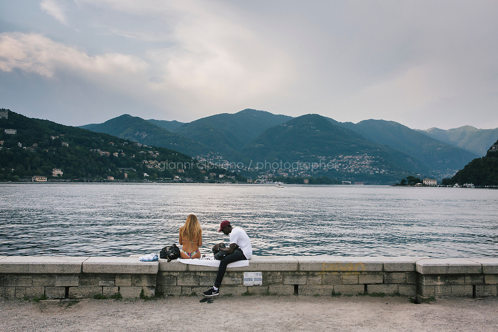 COMO, ITALY - 21 JUNE 2017: A tourist and a Sub-Saharan migrants are seen her together by Lake Como in Como, Italy, on June 21st 2017.<br /> <br /> Residents of Como are worried that funds redirected to migrants deprived the town&rsquo;s handicapped of services and complained that any protest prompted accusations of racism.<br /> <br /> Throughout Italy, run-off mayoral elections on Sunday will be considered bellwethers for upcoming national elections and immigration has again emerged as a burning issue.<br /> <br /> Italy has registered more than 70,000 migrants this year, 27 percent more than it did by this time in 2016, when a record 181,000 migrants arrived. Waves of migrants continue to make the perilous, and often fatal, crossing to southern Italy from Africa, South Asia and the Middle East, seeing Italy as the gateway to Europe.<br /> <br /> While migrants spoke of their appreciation of Italy&rsquo;s humanitarian efforts to save them from the Mediterranean Sea, they also expressed exhaustion with the country&rsquo;s intricate web of permits and papers and European rules that required them to stay in the country that first documented them.