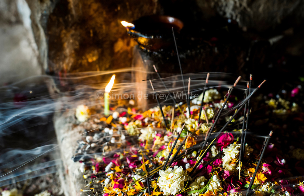 23rd April 2015, New Delhi, India. Smoke streams from incense sticks at a shrine dedicated to Djinn worship in the ruins of Feroz Shah Kotla in New Delhi, India on the 23rd April 2015<br /> <br /> PHOTOGRAPH BY AND COPYRIGHT OF SIMON DE TREY-WHITE a photographer in delhi<br /> + 91 98103 99809. Email: simon@simondetreywhite.com<br /> <br /> People have been coming to Firoz Shah Kotla to leave written notes and offerings for Djinns in the hopes of getting wishes granted since the late 1970's. Jinn, jann or djinn are supernatural creatures in Islamic mythology as well as pre-Islamic Arabian mythology. They are mentioned frequently in the Quran  and other Islamic texts and inhabit an unseen world called Djinnestan. In Islamic theology jinn are said to be creatures with free will, made from smokeless fire by Allah as humans were made of clay, among other things. According to the Quran, jinn have free will, and Iblīs abused this freedom in front of Allah by refusing to bow to Adam when Allah ordered angels and jinn to do so. For disobeying Allah, Iblīs was expelled from Paradise and called &quot;Shayṭān&quot; (Satan).They are usually invisible to humans, but humans do appear clearly to jinn, as they can possess them. Like humans, jinn will also be judged on the Day of Judgment and will be sent to Paradise or Hell according to their deeds. Feroz Shah Tughlaq (r. 1351&ndash;88), the Sultan of Delhi, established the fortified city of Ferozabad in 1354, as the new capital of the Delhi Sultanate, and included in it the site of the present Feroz Shah Kotla. Kotla literally means fortress or citadel.