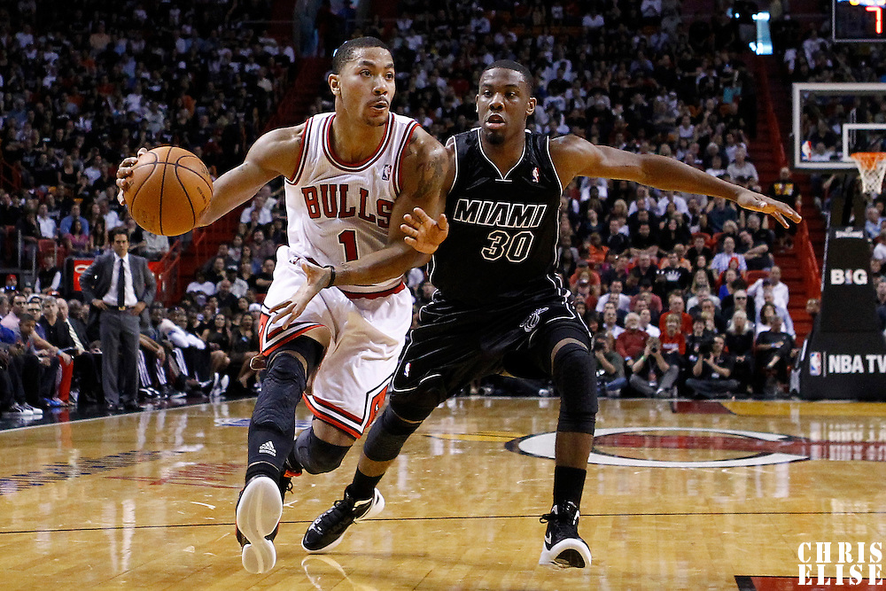 29 January 2012: Chicago Bulls point guard Derrick Rose (1) drives past Miami Heat point guard Norris Cole (30) during the Miami Heat 97-93 victory over the Chicago Bulls at the AmericanAirlines Arena, Miami, Florida, USA.
