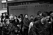 A crowd of people wait for a bus during rush hour in Chongqing.