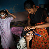 "Vasanti Shinde, age 26, who is HIV positive, at home with her daughters Vrinda, 8 and Shruda, 10. Shinde works for the Save Foundation which represents the rights of HIV positive people. ...Like many of the women who work for and with the Save Foundation, Vasanti Shinde, age 26, only found out that she was HIV positive after her husband became seriously ill with an AIDS-related illness five years ago. Vasanti's husband subsequently died. Vasanti now lives with her two younger daughters Shrudha, age 10, and Vrinda, 8, in the one-room home of her brother in Sangli city. Vasanti's elder daughter, eleven year old Shubhada is being brought up by her paternal grandmother and sees her mother during holidays. Vasanti knows that Shubhada is HIV negative and Shruda is positive but anxiety over the result means that she refuses to have Vrinda tested for HIV. For a monthly income of Rs.3500, Vasanti works as a field officer and counselor for the Save Foundation. She works in the positive-people's pharmacy for no pay. Her work with the Save Foundation entitles her access to a credit union which provides low interest loans covering medical expenses. Though first-line drugs and homeopathic medicine keep Vasanti healthy, she is prone to infection and recently suffered a bout of influenza. Vasanti is completely open about her HIV status and most of her neighbours know that she is HIV positive. Vasanti says that ""I used to feel like I was going to die. Now, because of the Save Foundation, I feel like I'm going to live."" ..Photo: Tom Pietrasik.Sangli, Maharashtra. India.August 28th 2008."