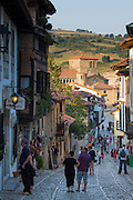 Tourists walk past medieval buildings along cobbled street of Calle Del Canton in Santillana del Mar, Cantabria, Northern Spain