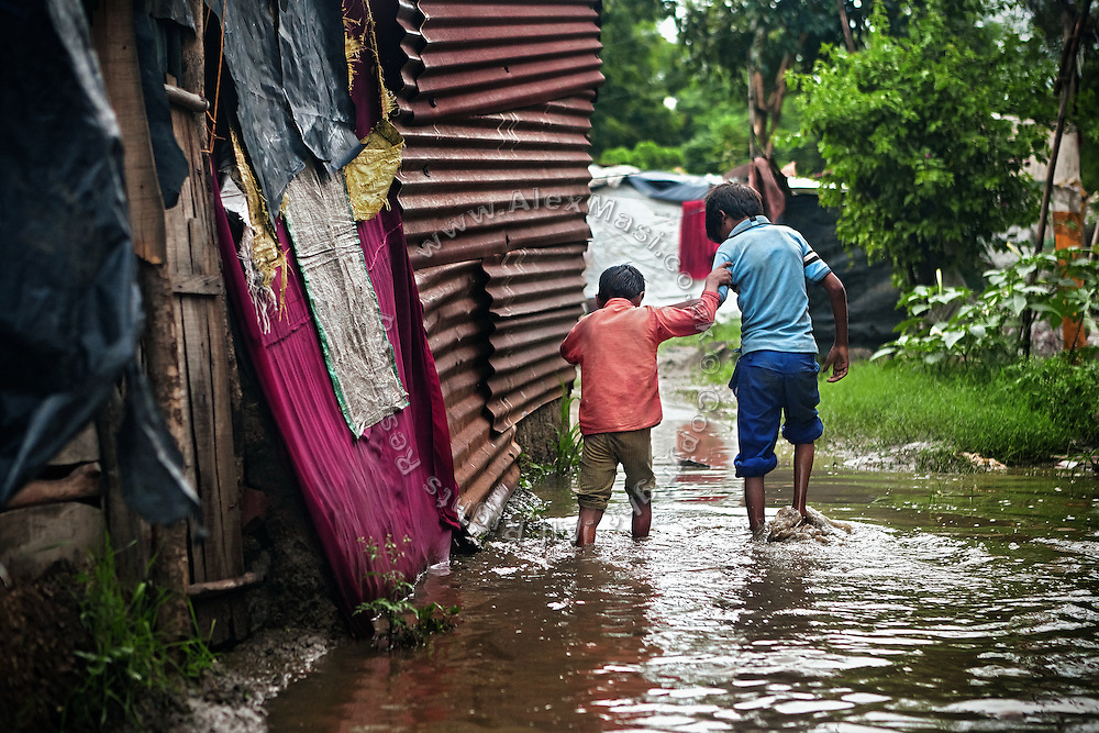 Two brothers are helping each other to cross flood waters in the path to their home in the impoverished Oriya Basti Colony in Bhopal, Madhya Pradesh, near the former Union Carbide (now DOW Chemical) industrial complex, site of the infamous 1984 gas disaster.