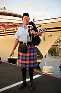 Freeport, New York, USA. September 10, 2014. A member of Wantagh American Legion Pipe Band plays during a dockside remembrance ceremony in honor of victims of the terrorist attacks of September 11 2001, at the boat Miss Freeport V, on Freeport's Nautical Mile. Further ceremonies were held on board the vessel, which sailed from the Woodcleft Canal on the South Shore of Long Island, on the eve of the 13th Anniversary of the 9/11 attacks.