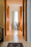 A contemporary home features a hallway with light wood floors, fir trimmed doorways and a light at the end of the hallway.