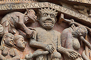 Hell, with the devil, an adulterous couple and a miser being hanged by his purse, early 12th century Romanesque, carved by the Master of the Tympanum, from the tympanum of the Last Judgement above the portal on the West facade of the Abbatiale Sainte-Foy de Conques or Abbey-church of Saint-Foy, Conques, Aveyron, Midi-Pyrenees, France, a Romanesque abbey church begun 1050 under abbot Odolric to house the remains of St Foy, a 4th century female martyr. The church is on the pilgrimage route to Santiago da Compostela, and is listed as a historic monument and a UNESCO World Heritage Site. Picture by Manuel Cohen