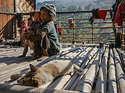 A tatooed Chin woman with her child and puppy on the porch of her hillside home. Chin State, Myanmar.