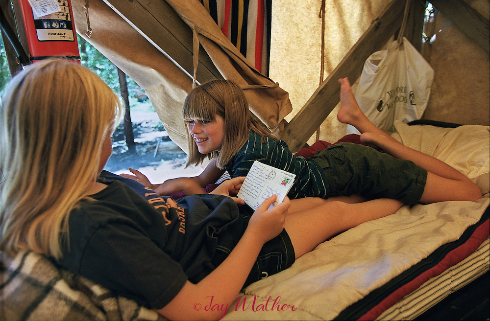 Camp friends Gianna Pinotti (cq), 10, and Karalyn Murphy (cq), 11, both from Jackson, sprawl together on a bunk to read notes and letters from home during their stay at Camp Menzies Girl Scout Camp.  A couple of hours each afternoon is set aside for the girls to rest and relax with campmates.  June 28, 2000.