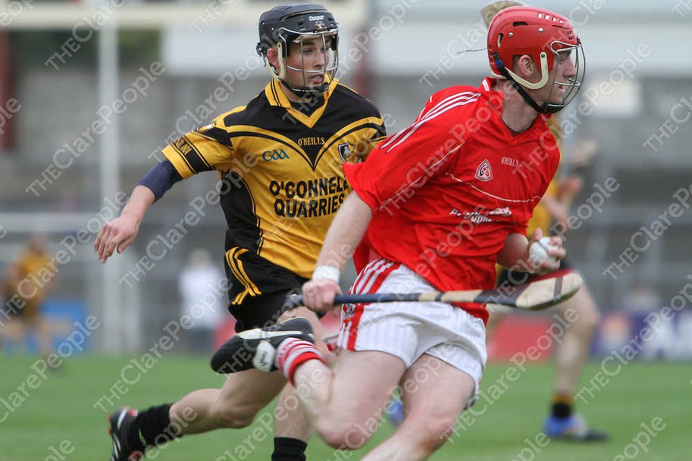Clonlara's Cathal O'Connell puts Crusheen's John Brigdale under pressure as he clears his line. - Photograph by Flann Howard