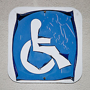decal outside of the Abita Springs postoffice designating parking space for handicapped customers is weathered by sun and the elements