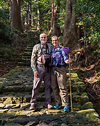 "Tom & Carol on a Kumano Kodo pilgrimage route. Kumano Nachi Taisha shrine was built in homage to Nachi-no-Taki waterfall's kami (spirit god). Don't miss the iconic view of thundering Nachi-no-Taki waterfall (133m, Japan's tallest) paired with Seigantoji pagoda, in Nachikatsuura, Higashimuro District, Wakayama Prefecture, Japan. Kumano Nachi Taisha shrine fuses Buddhist and Shinto influences along the 1000+ year pilgrimage routes of Kumano Kodo. The ""Sacred Sites and Pilgrimage Routes in the Kii Mountain Range"" form an impressive entry on UNESCO's List of World Heritage Sites. Access: by bus from Nachi Station (20 min) or Kii-Katsuura Station (30 min). Ask driver to stop at base of the Daimonzaka trail (""Daimonzaka"" stop); or at the entrance to Nachi Waterfall (""Taki-mae""); or at the bus terminus 10 minutes climb below Nachi Shrine (""Nachi-san""). Cars can park at Seigantoji Temple. I recommend this remarkably scenic, short walk (3.5 km with 265 meters gain): starting from Daimon-zaka bus stop, ascend a stone-paved path, humbled by massive evergreens, up to the gates of Nachi Taisha shrine; then descend to the falls, at Taki-mae bus stop.  To license this Copyright photo, please inquire at PhotoSeek.com."