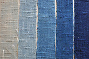 Indigo textile colour chart, using strips of fabric dyed using indigo, by fabric artist Betty de Paris, in her studio at Cite Aubry, in the 20th arrondissement of Paris, France. The Japanese indigo vat is a traditional dyeing technique using indigo leaf compost, a vegetal process involving no chemicals. Betty de Paris learned her art of traditional stencil dyeing and finishing from a master in Kyoto, Japan. Working as an artist, designer, consultant and Japanese interpreter, she has participated in numerous museum projects and workshops, regularly exhibits her work and speaks at international conferences. Picture by Manuel Cohen