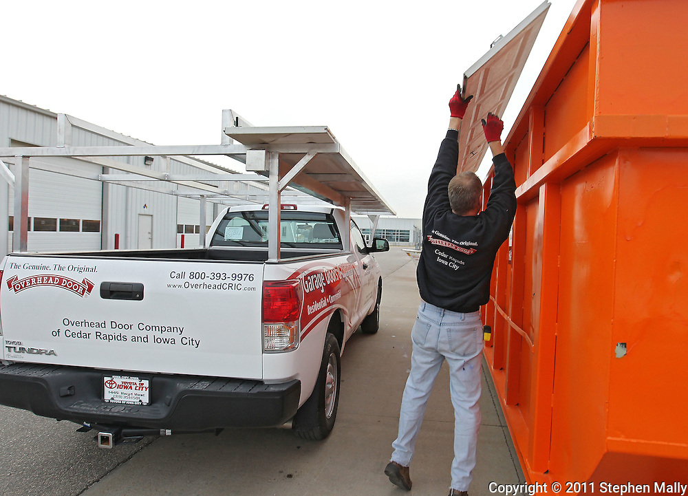 Leon Noska (back towards camera) and Brent Pettigrew (not visible) both of Cedar Rapids, toss a section of a garage door into a metal recycling bin at Overhead Door Company, 6515 4th Street SW in Cedar Rapids on Monday afternoon, November 21, 2011. (Stephen Mally/Freelance)