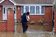 © Licensed to London News Pictures. 09/02/2014. Wraysbury, UK. A man heads back to his home.  Flooding in Wraysbury in Berkshire today 9th February 2014 after the River Thames burst its banks. Photo credit : Stephen Simpson/LNP