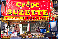 Lemonade and crepe vendor  preoccupied with his mobile device at the 92nd street Y street fair on Lexington Avenue.