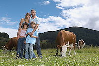 Parents with children (7-9) embracing in field with cows portrait