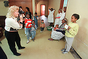 1/5/01 -- (PHOTO BY MIKE FENDER) w/ story, slug: AFRICA, file: 62040 // Cheryl Carter-Shotts, left, photographs children at the Kebebe Tsehay orphanage in Addis Ababa on a trip to Ethiopia in January. She uses the photos in newsletters to try and find homes for the orphans.