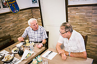 "NAPLES, ITALY - 12 SEPTEMBER 2018: (L-R) A customer chats with Gaetano Aiese, co-owner of the Taverna del Buongustaio, a tavern in Naples, Italy, on September 12th 2018.<br /> <br /> Taverna del Buongustaio was founded in the 1930s by wine producer of the province of Caserta. Gaetano Aiese and his daughter Giusy have been managing the tavern since 1996. Customers of the Taverna are professors of the nearby University, students, merchants and employees of via Toledo, the commercial street right around the corner. Giusy and her father Gaetano decided to invest in the traditional Neapolitan cuisine. ""I learned cooking from my dad. And my dad learned cooking from his mother"", Giusy said."