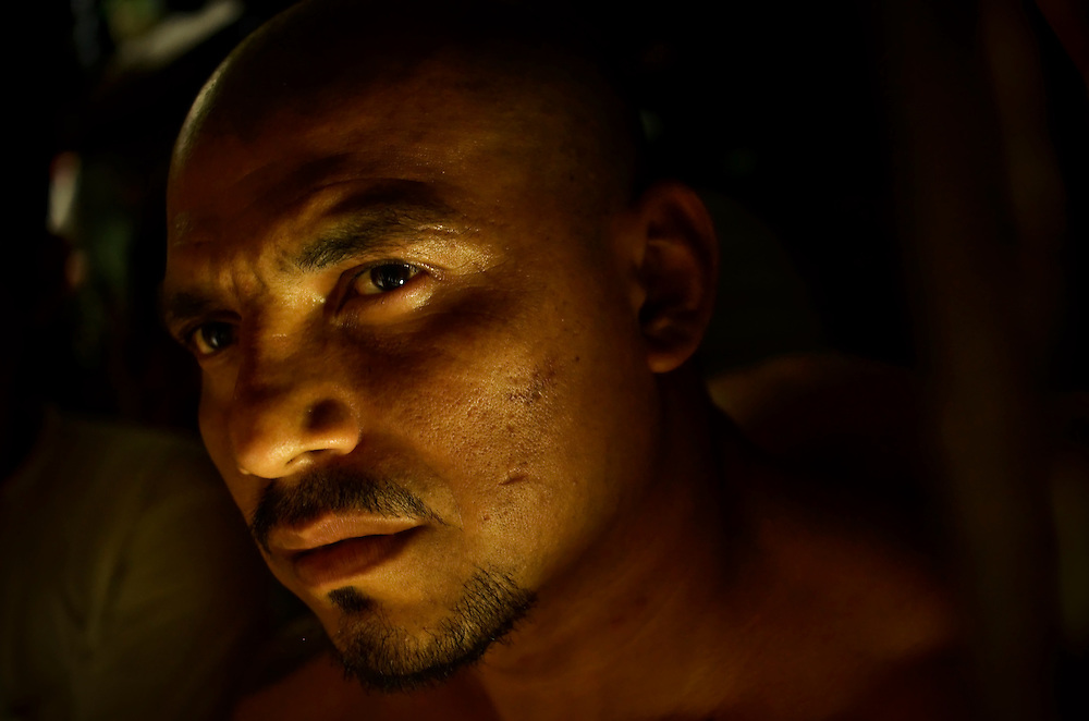 A member of the Mara 18 gang incarcerated in Izalco men's prison in El Salvador stares out of his cell at night.