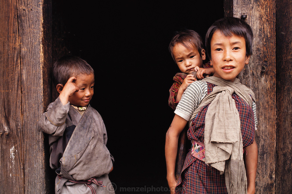Namgay and Nalim's family in Shingkhey Village, Bhutan. (Some of their children, from left to right): Their grandson Chato Geltshin, and daughter Bangam (holding her younger sister Zekom). From Peter Menzel's Material World Project.