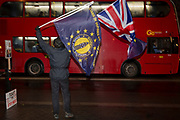 While MPs debate the Brexit Withdrawal Bill and ultimately vote in the House of Commons, a oro-EU Anti-Brexit protester waves EU and Union Jack flags to passing commuters outside Parliament, on 13th December 2017 in London, England.