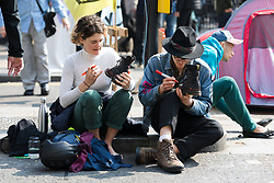 © Licensed to London News Pictures. 17/04/2019. Environmental activists from the Extinction Rebellion movement write on their boots as they continute to protest and block the road at Oxford Circus as part of a series of direct actions taking place across the capital. The protests demand urgent action from governments on climate change. Photo credit: Vickie Flores/LNP