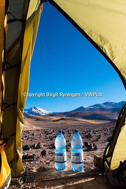 Two bottles of frozen water in the tent door. Camping in the Atacama desert, Chile