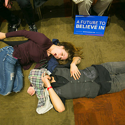 Dani Chapin (top) yawns as she lays on the Boise Centre floor with Josh Ferryman (bottom) while waiting for the first ballot results of the Idaho Democratic caucus in Boise, Idaho. A heavy voter led to the late results in the caucus which started at 7pm. As of 11:18, the first ballot results had not been announced. Ferryman got in line to vote at 3pm and Chapin joined him at 5pm. Tuesday March 22, 2016