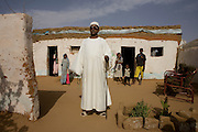 "Mr Matar Mohammed, a former farmer from Taweela, a Darfur village in the 4 sq km Abu Shouk refugee camp, (disputedly) home to 38,000 displaced persons, on the outskirts of Al Fashir. Mr Mohammed was once a successful farmer who grew tobacco and sorghum and has occupied this house with his 14 family members since May 2004, surviving on twice a day aid hand-outs. Many family members and friends have been killed . "" We had a good life,"" he says adding ""we would go back if security was guaranteed .."""