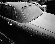 A car dusted with snow. An image from S. R. Shilling II's photographic series documenting his experience observing United State's largest city, New York.