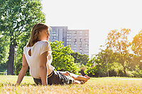 Rear view of young attractive businesswoman sitting on the grass while watching the sunset