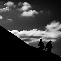 Two people walking uphill along a darkened wall with white fluffy clouds behind them.
