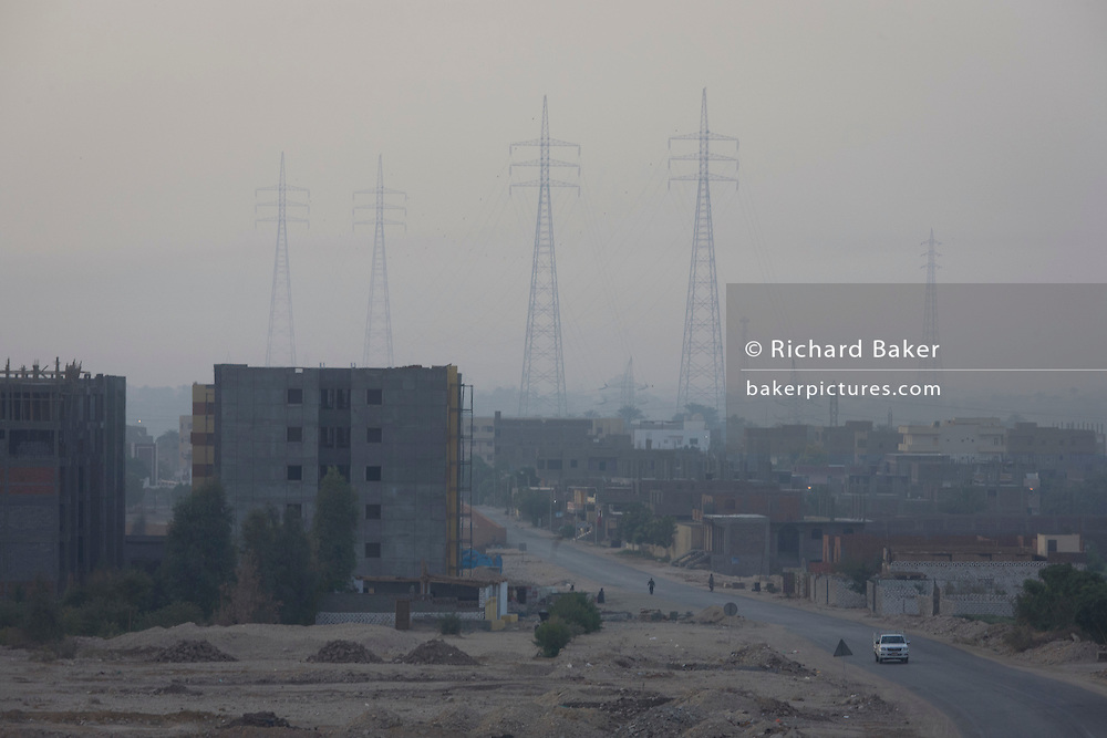 Looking east from the West bank of the river Nile, of electricity power pylons and local housing in the modern city of Luxor, Nile Valley, Egypt.