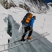 Brent Bishop crosses a ladder over a massive crevasse in the Western Cwm on Mount Everest, Nepal.