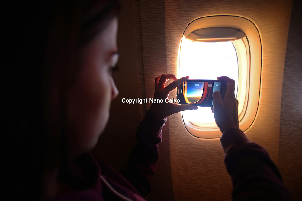 Young woman takes a photo through window during  flight