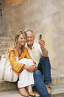 Couple on steps photographing selves with phone camera
