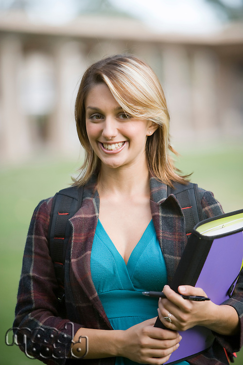 Young female student holding a book and looking at camera
