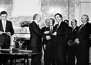 After their win in the recent general election, the new Fianna Fáil government, under the leadership of Charles Haughey, is sworn in and given their seals of office at a ceremony in Áras an Uachtaráin. President Hillery presents the seal of office to Bertie Ahern at the ceremony in the Arás.<br />