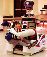 Billy Dyak, 10, sits on the lap of a robot that came to visit Queen of the Universe school in Levittown on Wednesday morning..Copyright 1997 William T. Cain