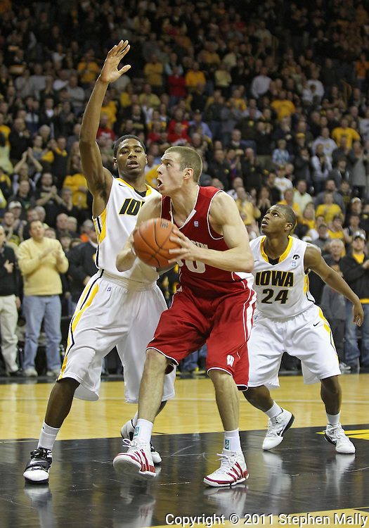 February 09 2011: Wisconsin Badgers forward Jon Leuer (30) looks to put up a shot as Iowa Hawkeyes forward Melsahn Basabe (1) defends during the first half of an NCAA college basketball game at Carver-Hawkeye Arena in Iowa City, Iowa on February 9, 2011. Wisconsin defeated Iowa 62-59.