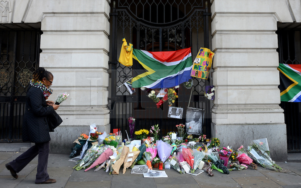© Licensed to London News Pictures.06/12/2013. London, UK. Members of the public lay flowers at the South African Embassy, London to pay tribute to late former South African president Nelson Mandela following his death in Johannesburg.Photo credit : Peter Kollanyi/LNP