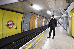 © Licensed to London News Pictures. 18/03/2020. London, UK. A commuter wearing a face mask waits for a train at Baker Street station during the morning rush during the Coronavirus outbreak. Photo credit: Ray Tang/LNP