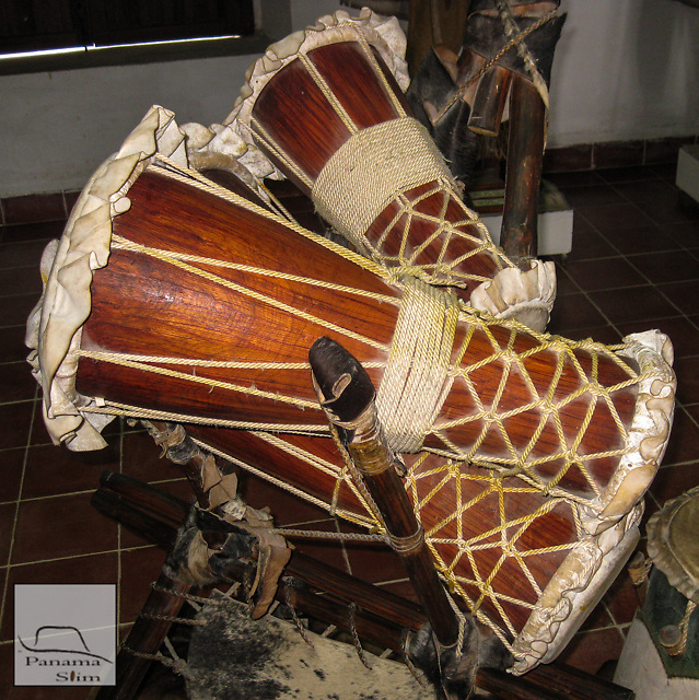 The Bata drums are a doubled-head set of three drums played in both Lucumi and continental Yoruba ritual space.  In Lucumi practice, the drums are hand beat, while continental practice sometimes use a leather strap.  Bata are primarily sacred drums that have been extensively prepared (although unwashed sets are available and played).  The Sacred Bata are dedicated to the Orisha A&ntilde;a.  Only those initiated to A&ntilde;a can even touch a set of Sacred Bata.�<br /> �<br /> The three drums are called: Iya (largest), Itotele (middle) and Okonkolo (smallest).