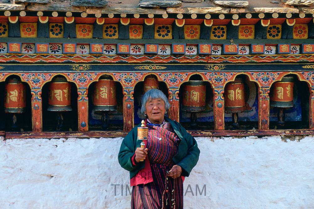Woman holding prayer wheel at Kyichu Temple, Paro, Bhutan